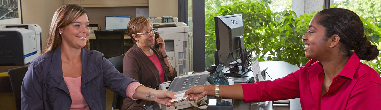 Metro Imaging patient presenting insurance card at front desk.